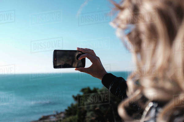 Young woman using a smartphone on a coast Royalty-free stock photo