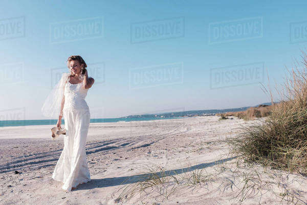 Bride walking on a sandy beach Royalty-free stock photo