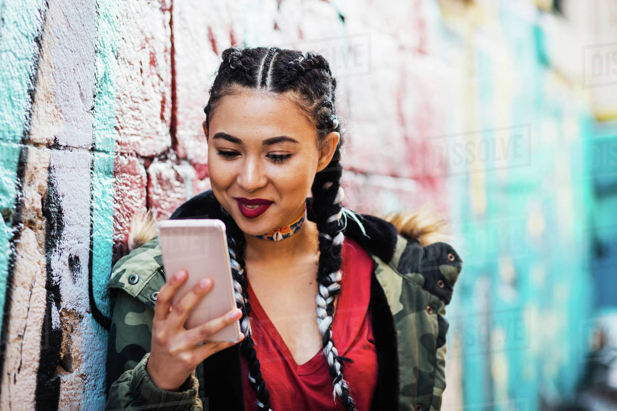 Portugal, Lisbon, Smiling young woman looking at smartphone, leaning against wall Royalty-free stock photo