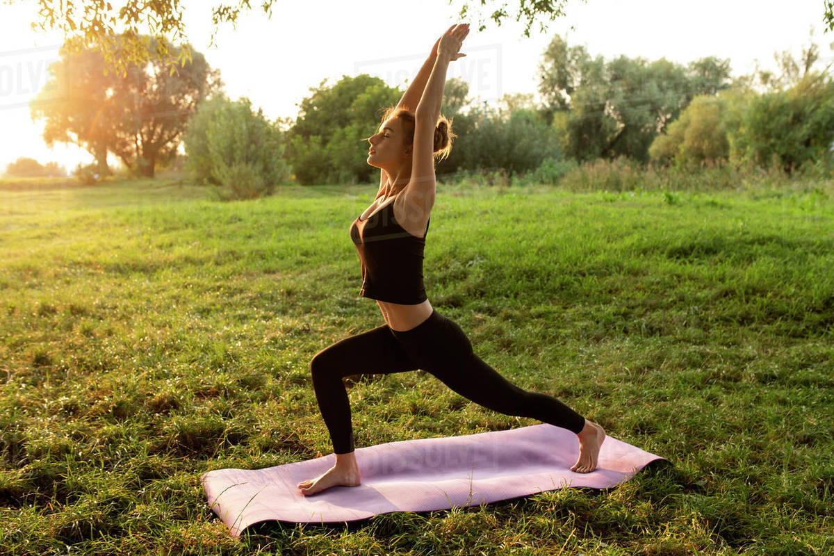 Young Woman Practicing Yoga In Park Stock Photo Dissolve