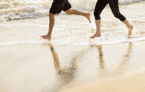 Couple running on beach, low section Royalty-free stock photo
