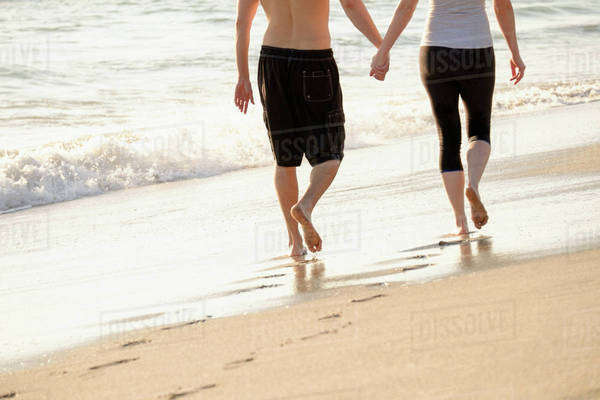 Couple walking on beach, low section Royalty-free stock photo