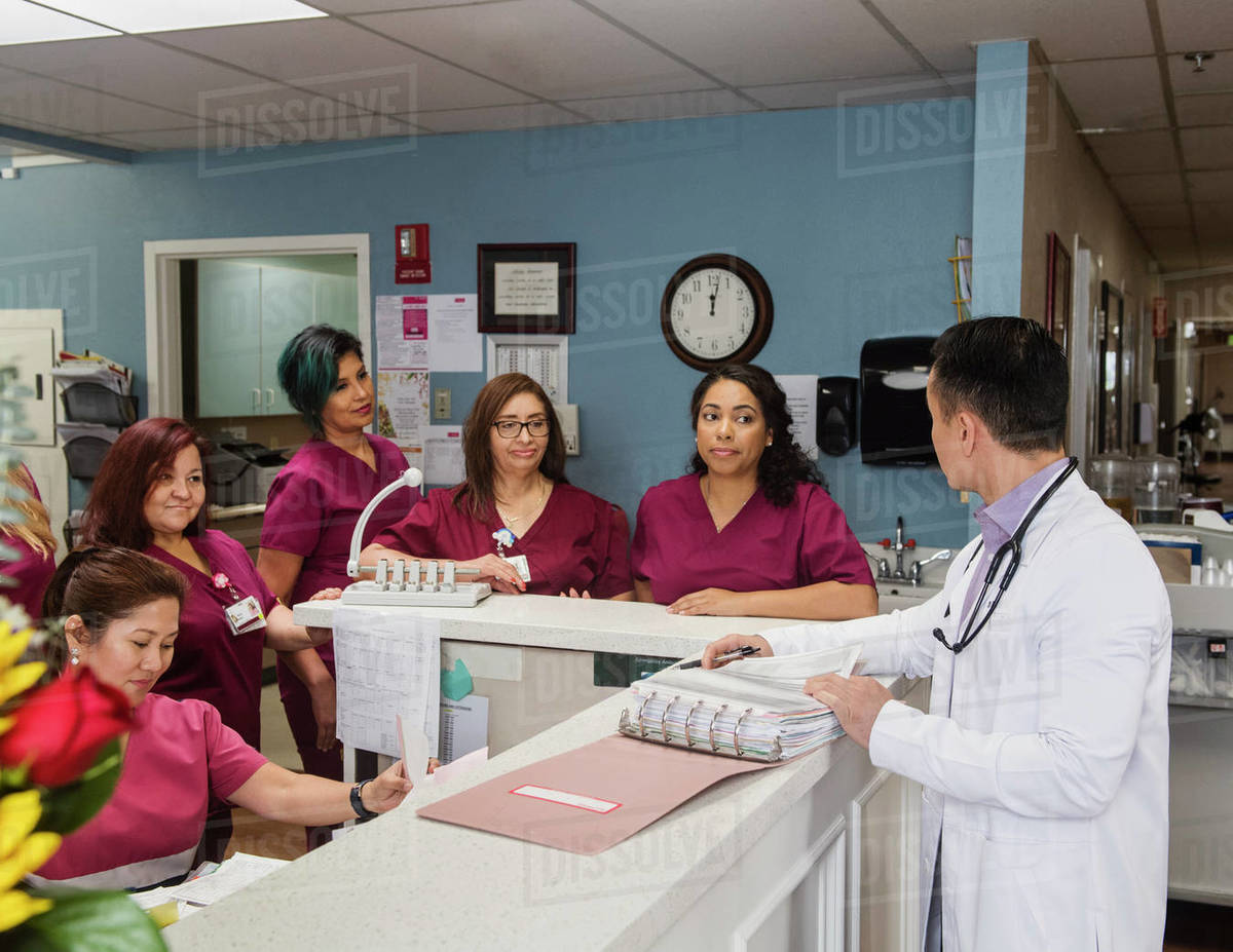Doctor and nurses at reception desk Royalty-free stock photo