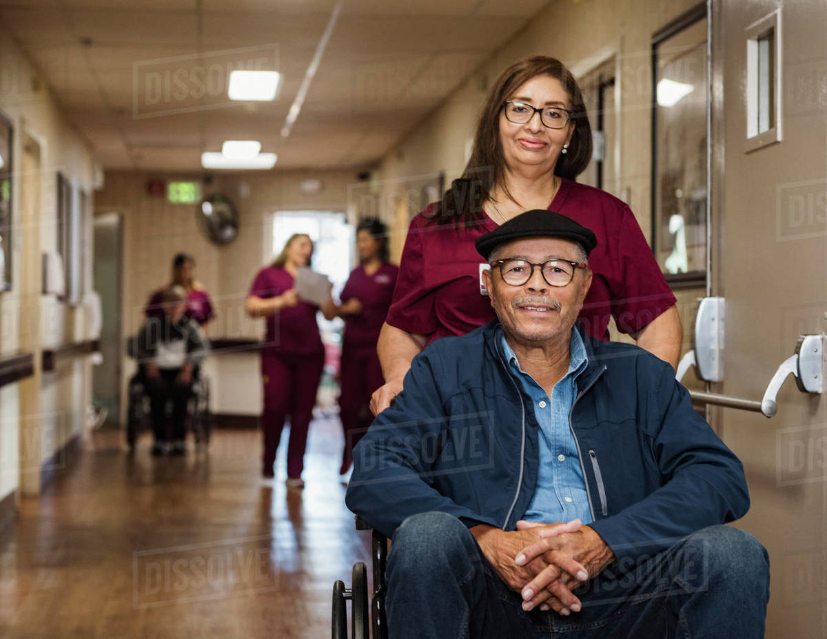 Nurse assisting senior man in wheelchair Royalty-free stock photo