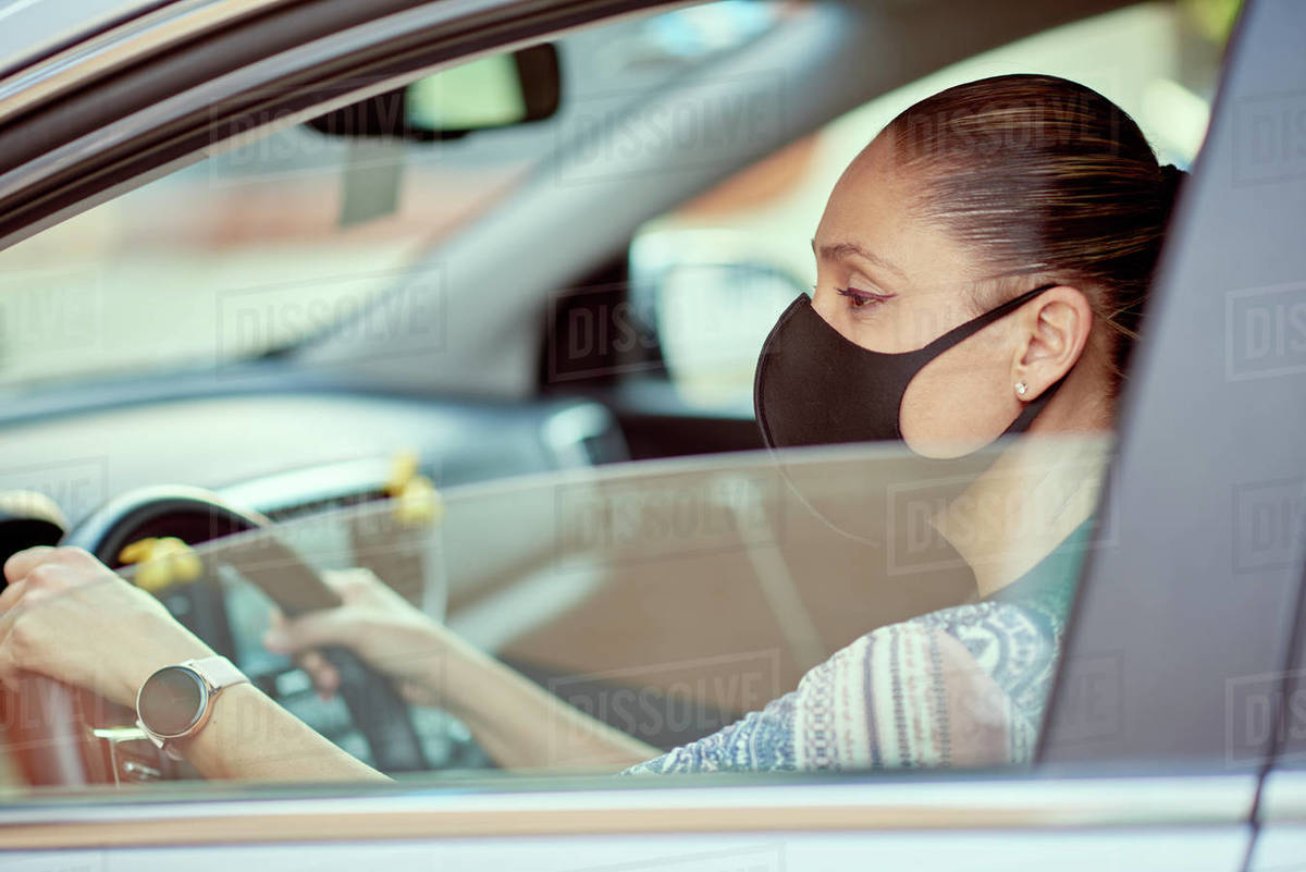 Woman with face mask driving car Royalty-free stock photo