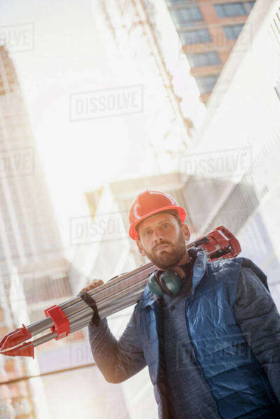 Portrait of construction worker carrying tripod on shoulder Royalty-free stock photo