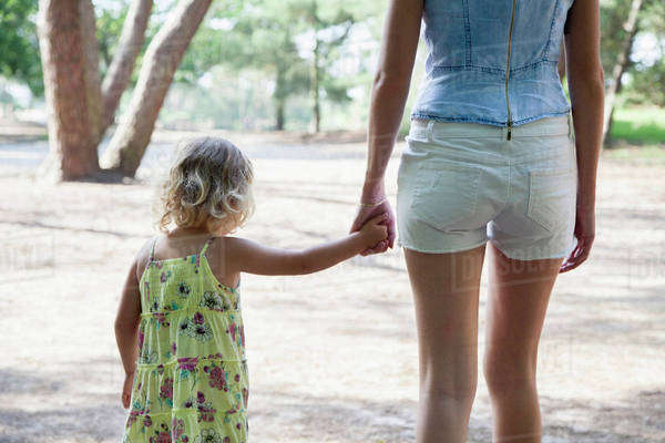Rear view of mother and daughter (2-3) holding hands Royalty-free stock photo
