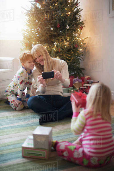 Mother with children (4-5, 6-7) opening christmas presents and taking photos Royalty-free stock photo