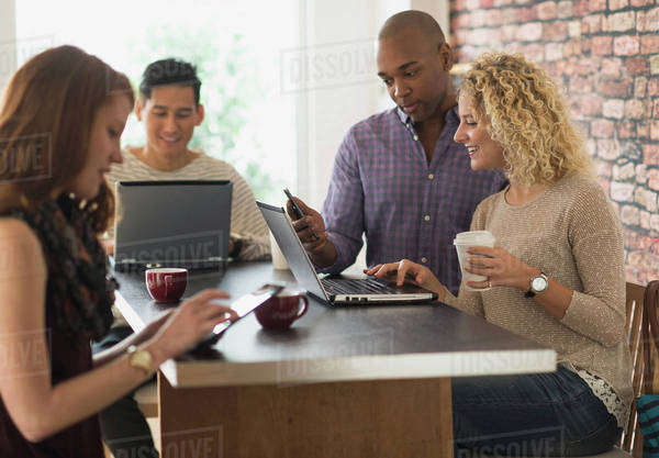 Friends sitting in cafe, using laptops and digital tablets Royalty-free stock photo