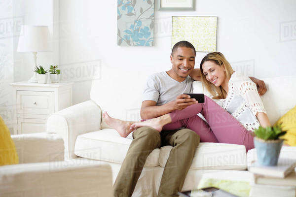 Mid adult couple looking at smart phone in living room Royalty-free stock photo