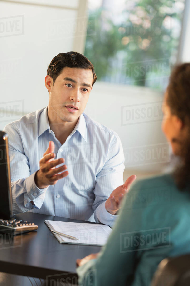 215977ff878e Man and woman talking at desk during job interview - Stock Photo ...