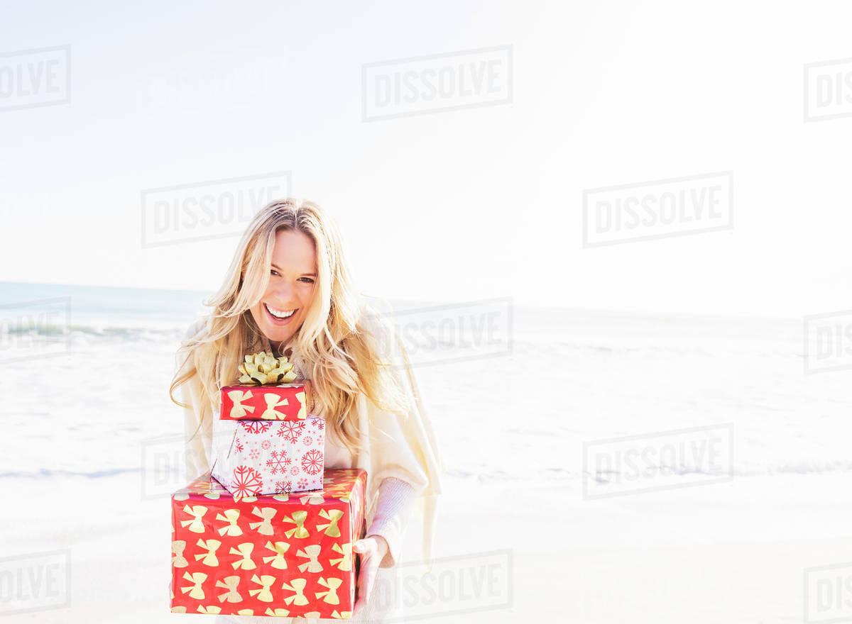 Portrait Of Smiling Woman Holding Presents On Beach