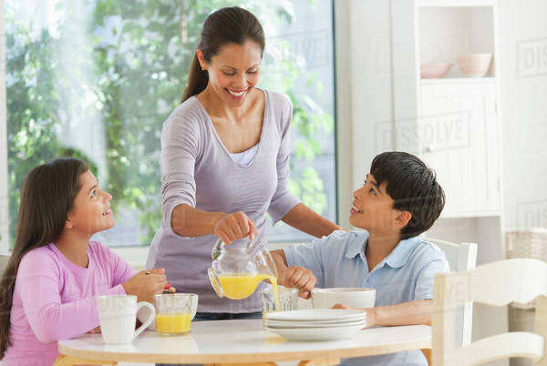 Mother with son (12-13) and daughter (10-11) having breakfast Royalty-free stock photo
