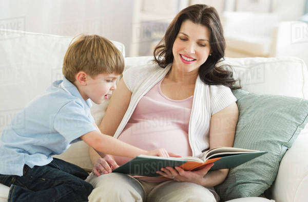 Mother and son (4-5) reading book on sofa Royalty-free stock photo