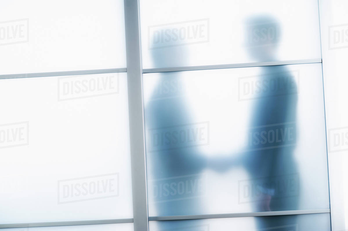 Silhouettes Of Two Businessmen Behind Glass Door Stock Photo