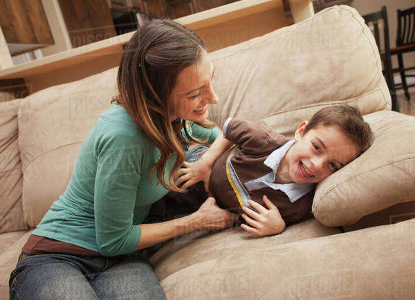 Mother tickling her son (6-7) on couch  Royalty-free stock photo