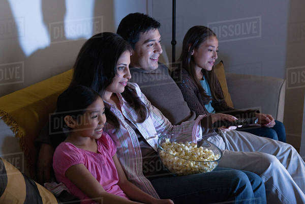 Family with two children (8-9, 10-11) watching tv on sofa Royalty-free stock photo