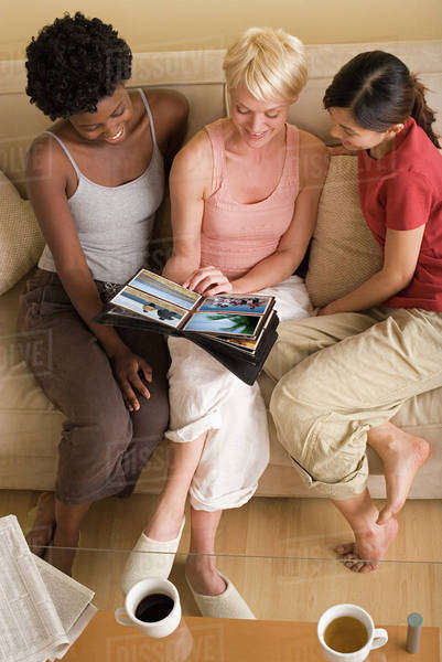 Three girlfriends looking at photo album Royalty-free stock photo