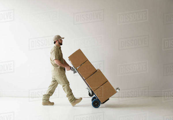 Delivery man walking with push cart Royalty-free stock photo