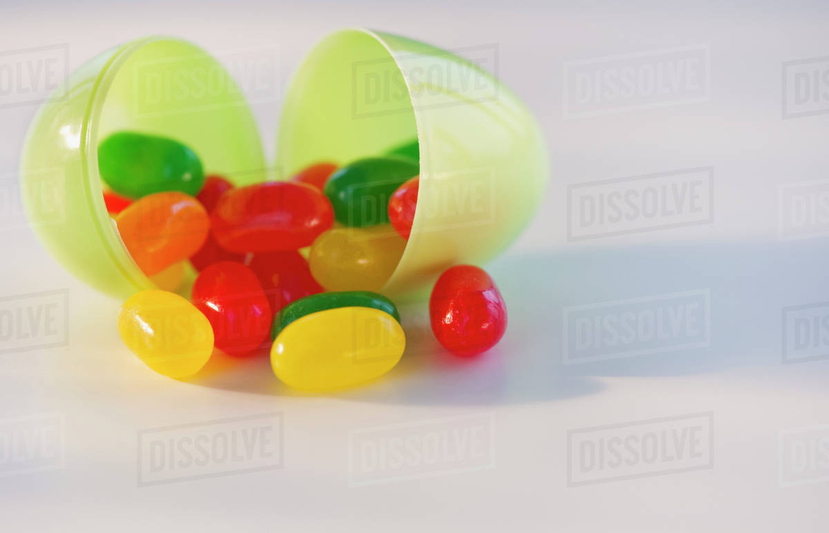 Jelly beans in a plastic Easter egg - Stock Photo - Dissolve