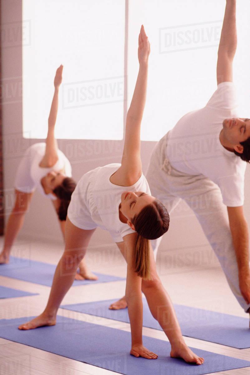 Three People Stretching On Yoga Mats Stock Photo Dissolve