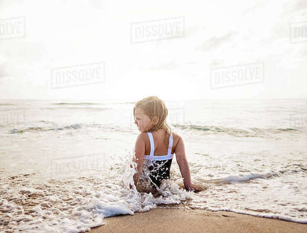Girl (4-5) sitting in water on beach Royalty-free stock photo