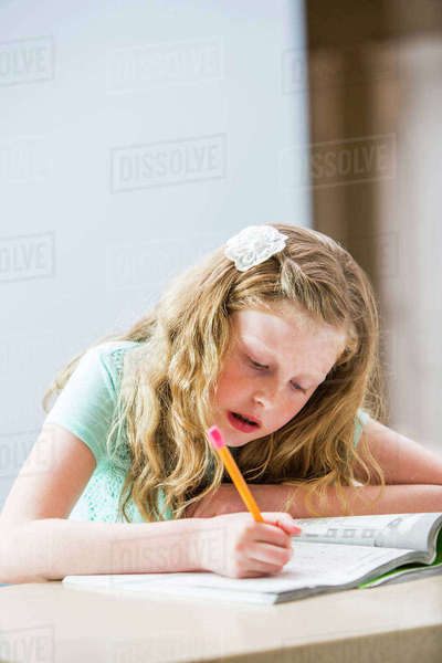 Blonde girl (8-9) doing homework at table Royalty-free stock photo