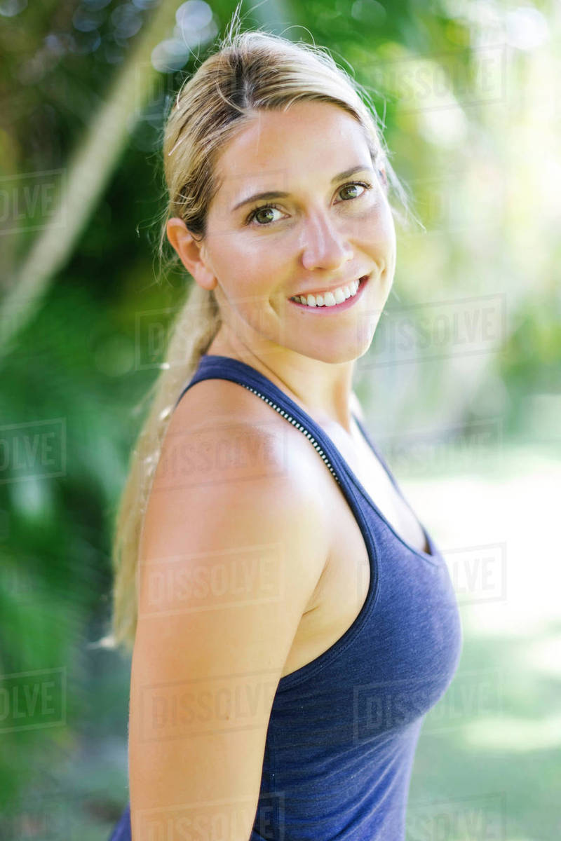 72642b5eda4c5 Blonde woman in tank top smiling - Stock Photo - Dissolve