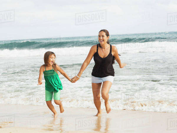 Girl (6-7) running on beach with mother Royalty-free stock photo