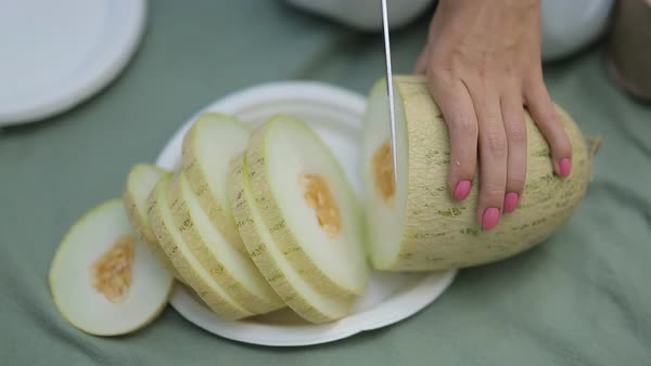 Close-up of girl with a knife cuts ripe juicy melon Royalty-free stock video