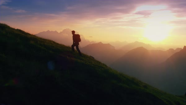Epic shot of a man hiking on the edge of the mountain as a silhouette in colorful sunset Royalty-free stock video