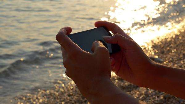 Close-up - Typing a message on phone at the beach Royalty-free stock video