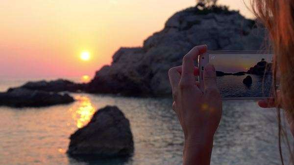 Young woman taking photo of the sunset with her phone on the beach Royalty-free stock video