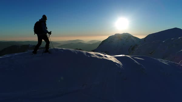 Aerial - Close up shot of young winter hiker arriving on top of snowy mountain peak at sunset Royalty-free stock video