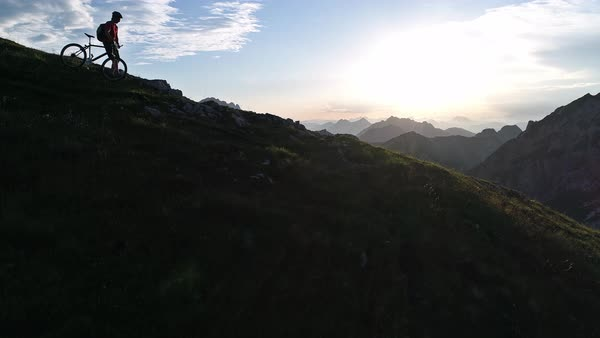 Aerial - Raising above mountain biker walking downhill with his bike on a steep mountain edge at sunset Royalty-free stock video