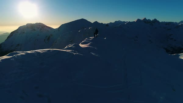 Aerial - Low flight over ridge around young male hiker standing on top of snowy mountain top at sunset Royalty-free stock video