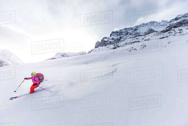 Female ski adventurer skis down powder snow slope. Royalty-free stock photo