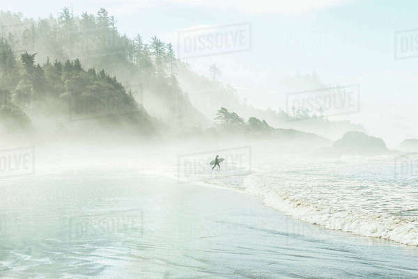Man with surfboard walking towards sea by mountain during foggy weather Royalty-free stock photo