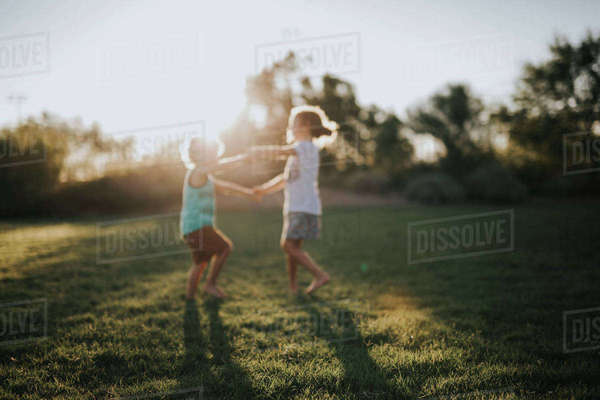 Happy siblings playing on grassy field in backyard Royalty-free stock photo