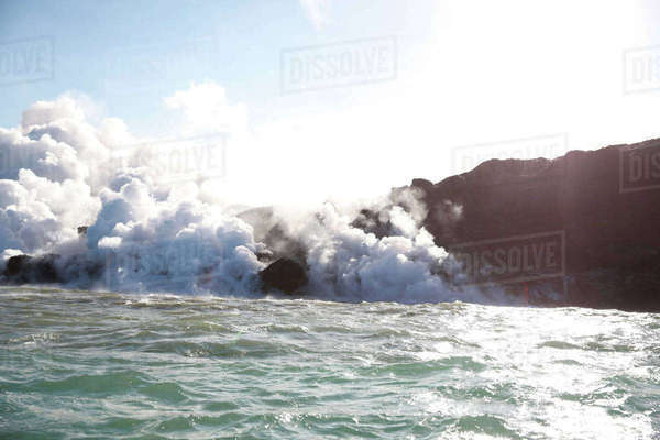 Steam emitting from rocks by sea against clear sky Royalty-free stock photo