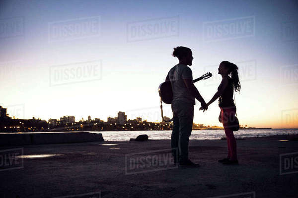 Silhouette couple standing at lakeshore against clear sky Royalty-free stock photo