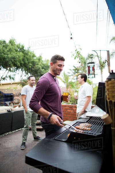 Man preparing food on barbecue grill while standing with friends in background Royalty-free stock photo