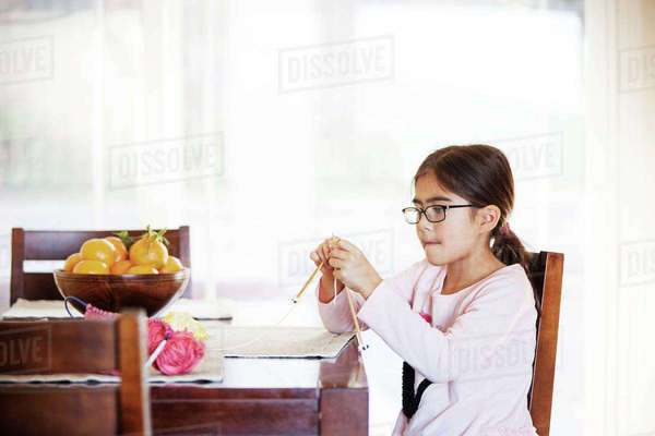 Girl knitting while sitting at table Royalty-free stock photo