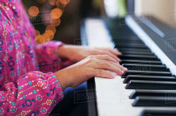 Midsection of girl playing piano while sitting at home Royalty-free stock photo
