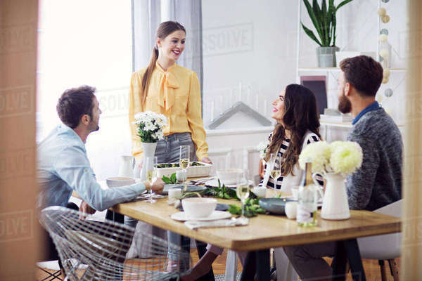 Happy friends looking at woman in lunch party Royalty-free stock photo