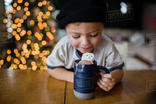 Happy boy looking in cup with marshmallow snowman at home Royalty-free stock photo