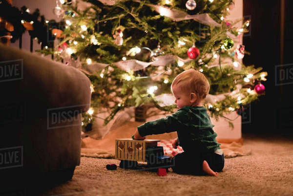 Side view of cute baby boy playing with toy truck by Christmas tree at home Royalty-free stock photo