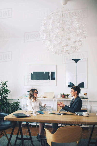 Businesswomen discussing while sitting at table in office Royalty-free stock photo