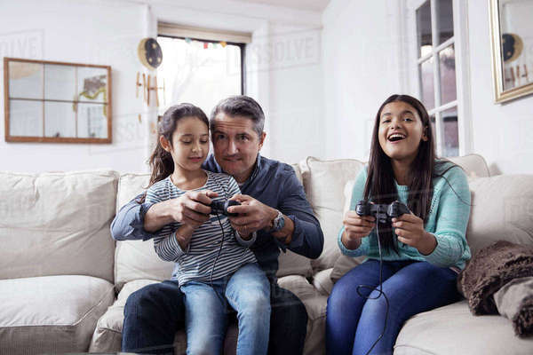 Girls with father playing video game while sitting on sofa at home Royalty-free stock photo