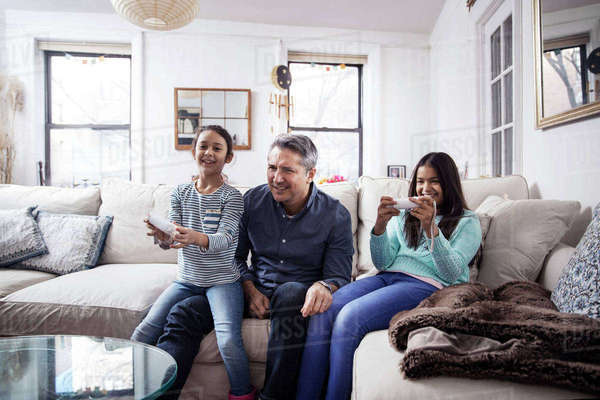 Daughters playing video game while sitting with father at home Royalty-free stock photo